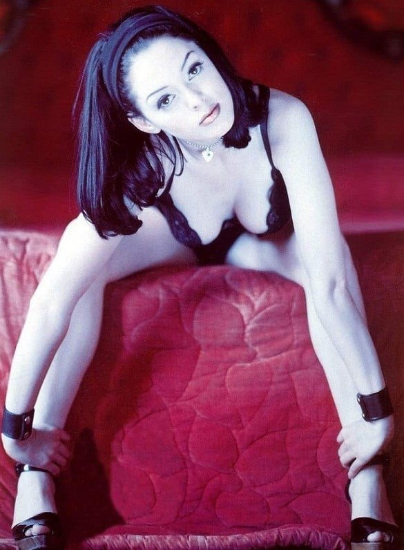 The sensual Rose McGowan on the edge of a bed wearing black heals and bra showing her cleavage