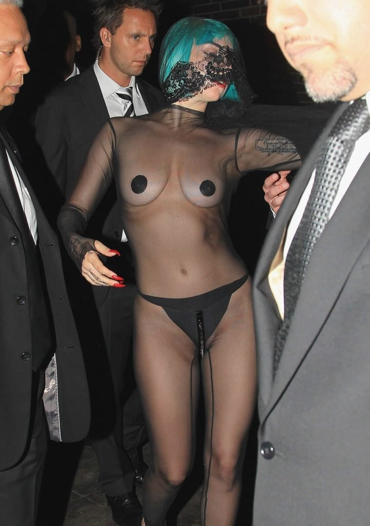 Lady Gaga in a see through dress covering her nipples with black spots wearing a turquoise wig