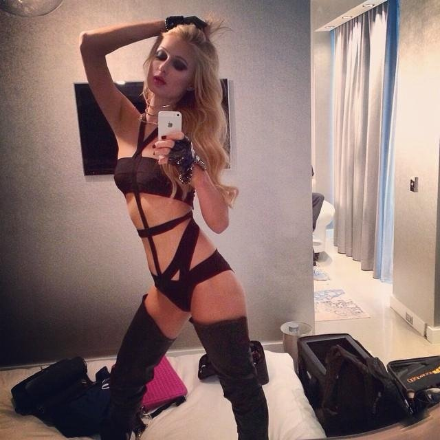 Paris Hilton standing sexy in a dominatrix outfit and thigh high boots