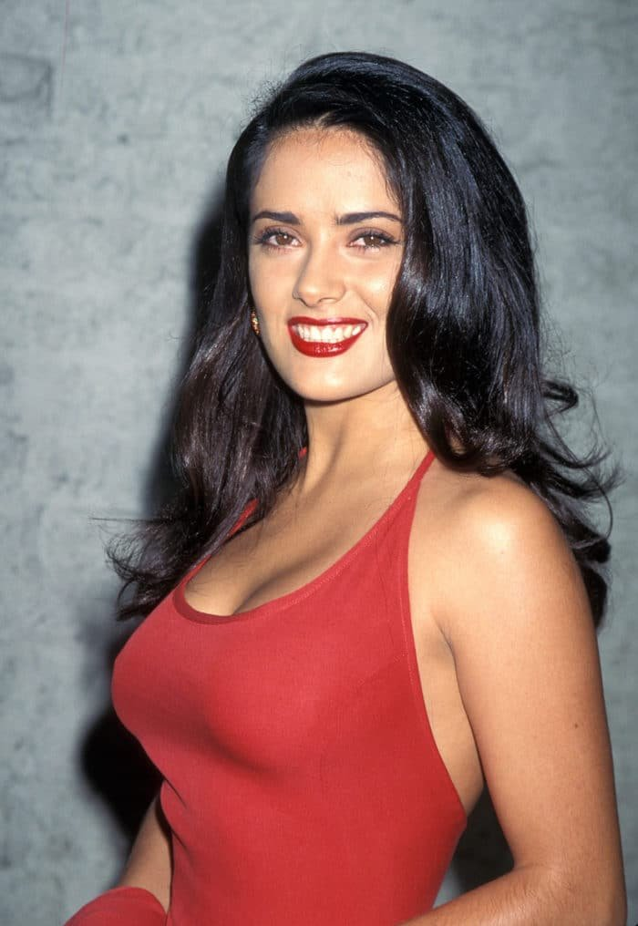 Gorgeous photo of Salma Hayek in red top with dark hair down wearing red lipstick