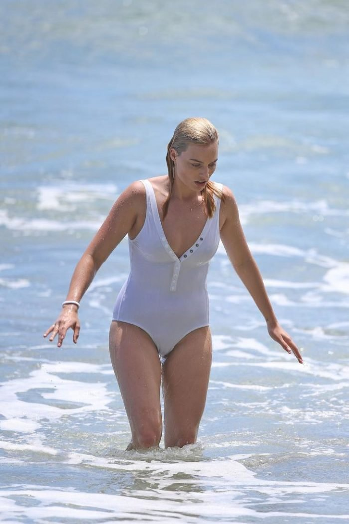 Margot Robbie in one piece bathing suit with nipples poking through