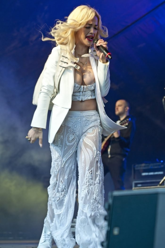 Rta Ora on stage singing with her nipple popping out of her outfit