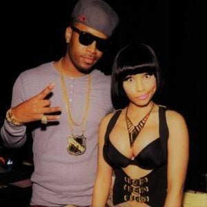 Safaree Samuels giving a peace sign to the camera and Nicki Minaj looking hot in sexy black outfit with bangs