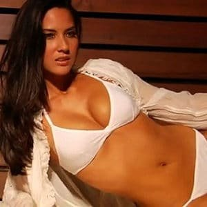 celeb olivia munn in white bikini modeling on her side with cleavage