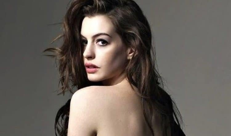 gorgeous celebrity anne hathaway poses topless and is looking back at the camera with a sexy look