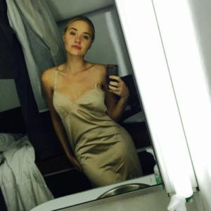 AJ Michalka taking a selfie in a gold slip dress