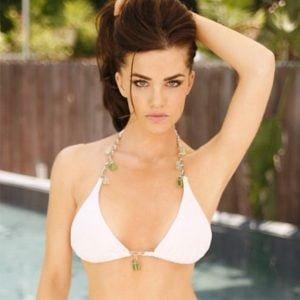 Jillian Murray in a white bikini top holidng her hair out.