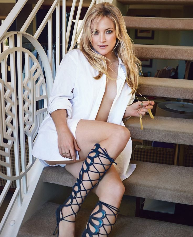 Kate Hudson sitting on staircase wearing a white jacket with no bra
