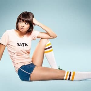 Kate Micucci sitting with her leg straigt wearing knee high socks