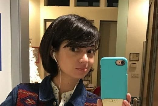 Kate Micucci taking a bathroom selfie in a jean jacket