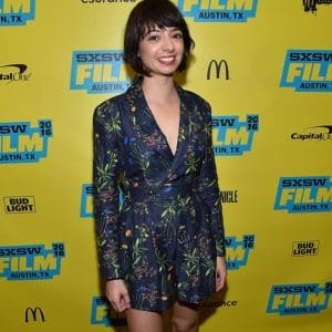 Kate Micucci wearing a blue wrap dress standing in front of a yellow background