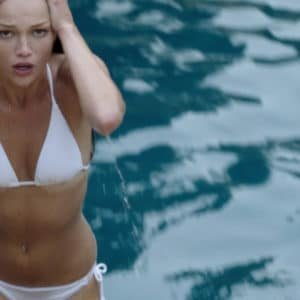 Lili Simmons in a white swimsuit getting out of a pool
