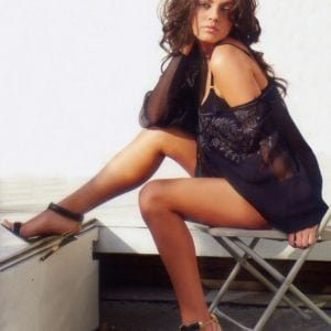 Mila Kunis sitting on a folding chair in black dress