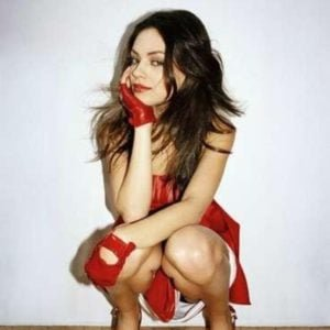 Mila Kunis squatting in red heels and dress