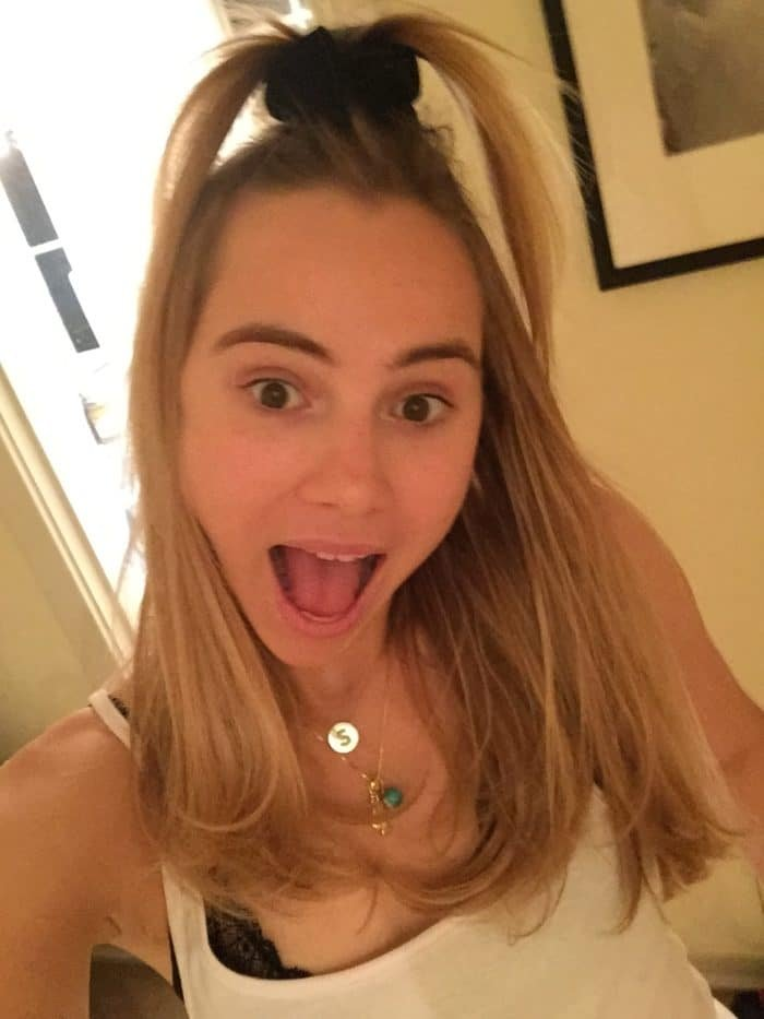 Suki Waterhouse taking a selfie with mouth open and hair in a top knot