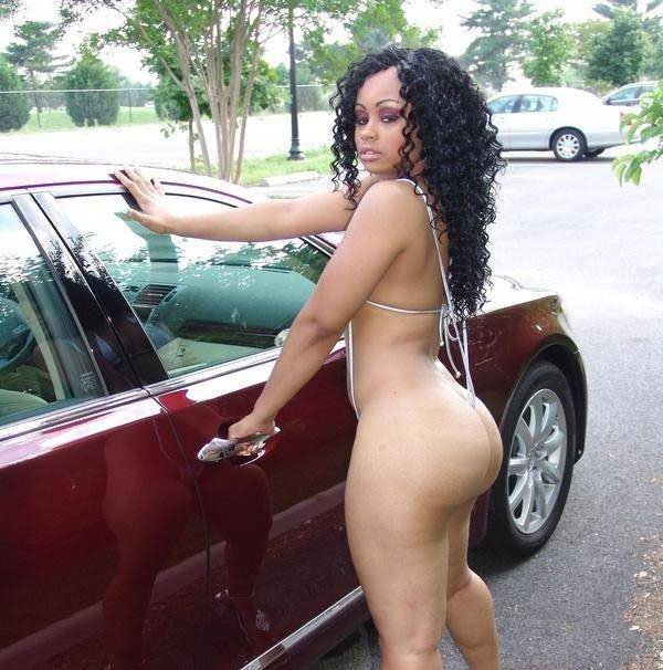 Blac Chyna standing naked in front of a car