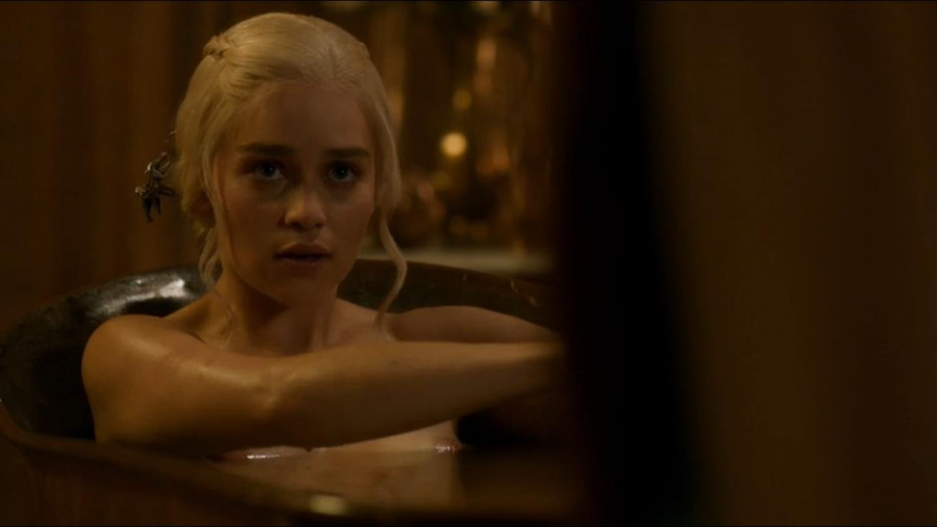 Emilia Clarke sitting bath tub with arms in front of chest