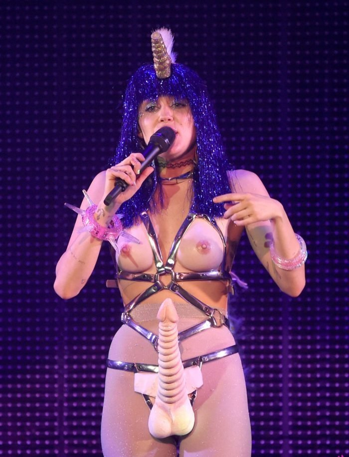 Miley Cyrus wearing a purple wig on stage