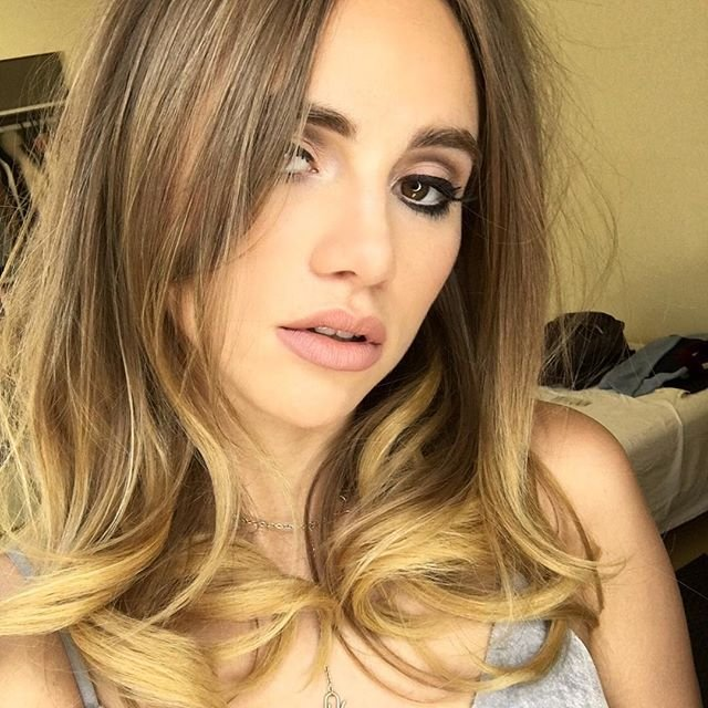 Suki Waterhouse selfie with pink lipstick and dark eyeliner giving a seductive face