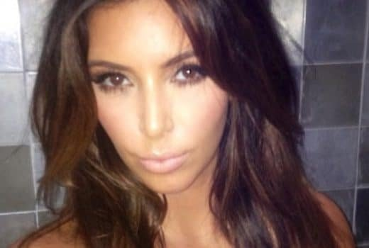 Kim Kardashian taking a selfie against a tiled wall