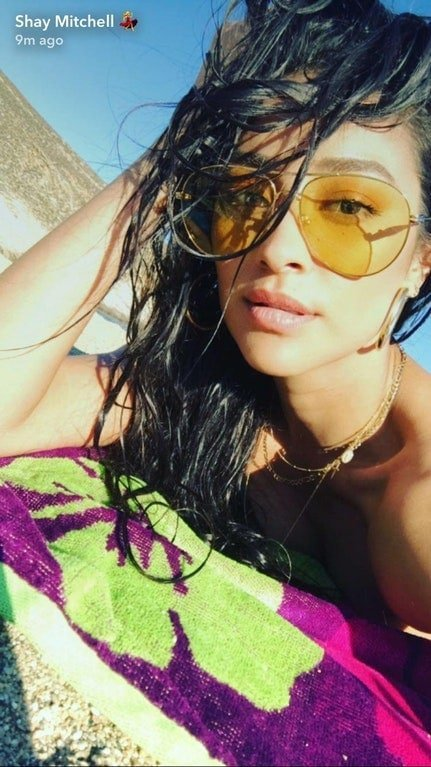 Shay Mitchell wearing yellow sunglasses and laying on a beach towel snapchat